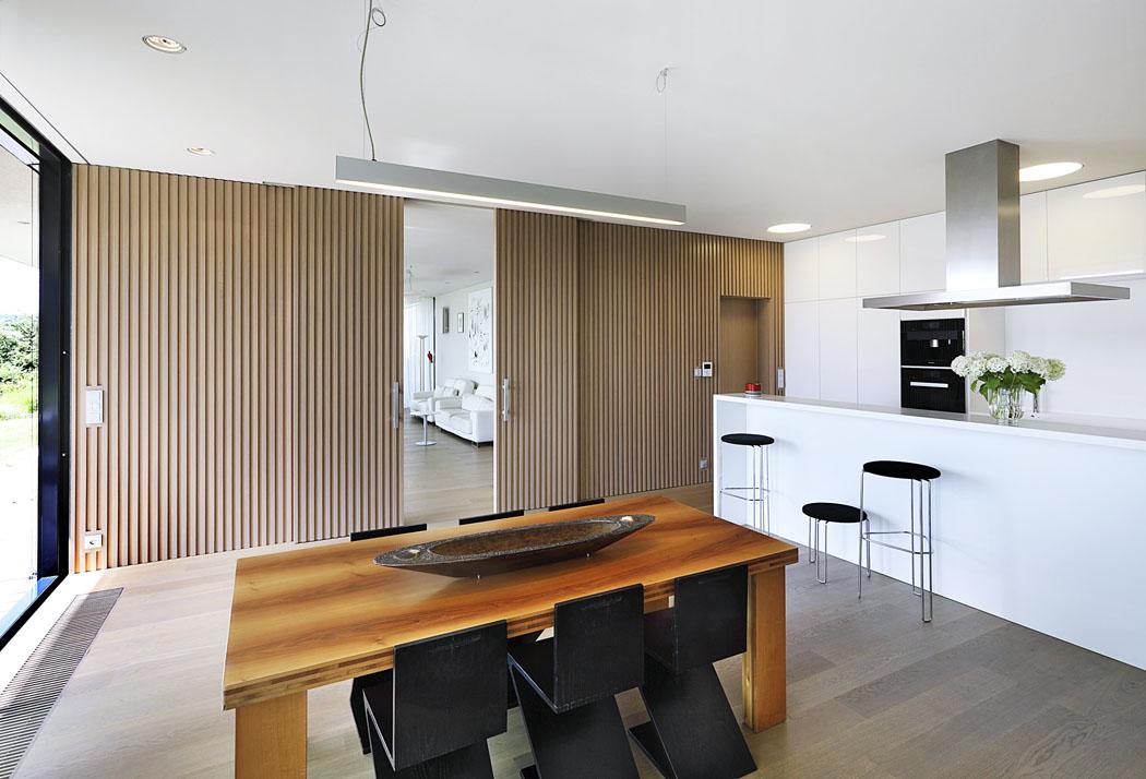 Kuchyňská část je odobývacího pokoje oddělena posuvnými dveřmi astěnou vyrobenou ztýchž profilů jako obklad fasády. Interiér domu se tak propojuje asjednocuje sexteriérem.