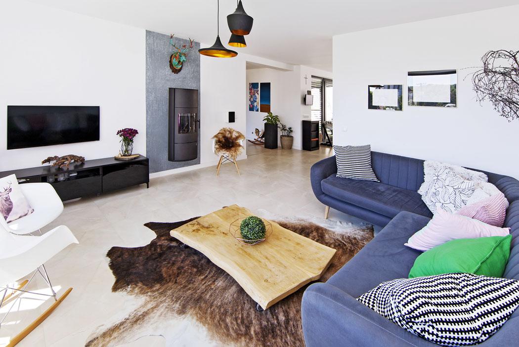 Společná obývací část, kuchyňská část a vstupní hala se prolínají jako spojité nádoby. Vybavení je jednoduché, ale barevné a nápadité. Plánovanou stěrku na podlaze nahradila velkoformátová keramická dlažba, je levnější a navíc ideální pro podlahové vytápění.