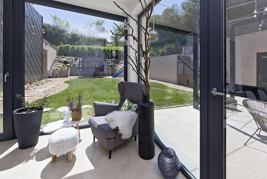 Mezi domem a skálou se nachází ze všech stran uzavřená dvouúrovňová zahrada s terasou, pergolou a travnatou plochou – hřejivá oáza odpočinku.