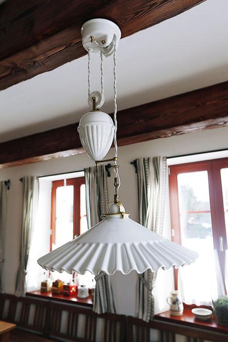 I na svítidlech si dal majitel záležet – na obrázku je zrestaurovaný porcelánový stahovací lustr z počátku 20. století, nechybí ani další svítidla vyrobená na zakázku v podobném stylu.