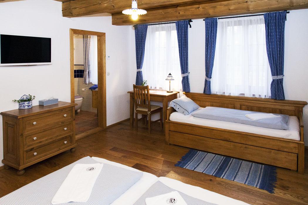 Pokoje jsou tematicky vybaveny i pojmenovány, na obrázku vidíte Modrý pokoj s dveřmi do koupelny. Nábytek v celém domě je vyroben na zakázku ve stylu našich prababiček.
