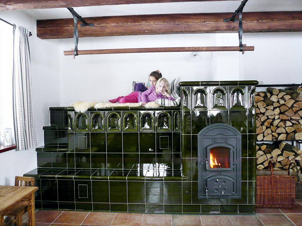 Kachlovou pec si majitel navrhoval sám, teplo je vyvedeno speciálními rozvody do místností vpodkroví. Na peci se dá také pohodlně ležet a oblíbená je i vyhřívaná lavice vpředu.
