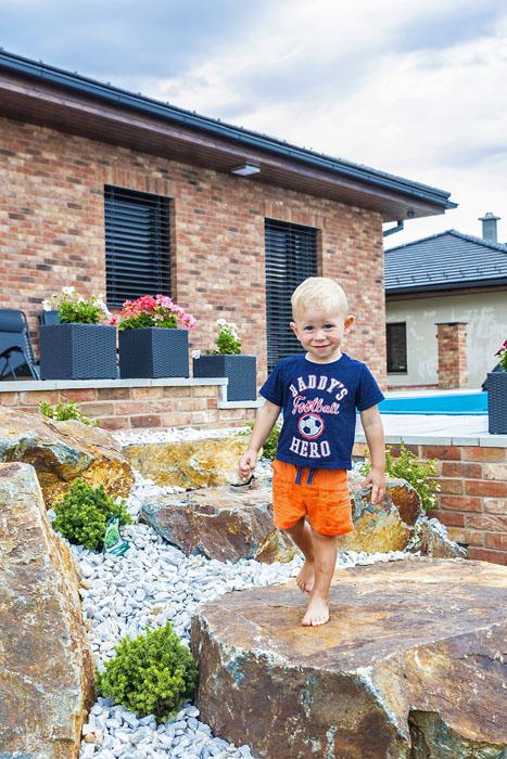 Na obrázku vlevo stojí syn pána domu na venkovním schodišti vytvořeném z obřích kamenů. Vedle je terasa s bazénem Mountfield a zajímavou pergolou se sloupky z kmenů stromů (1)