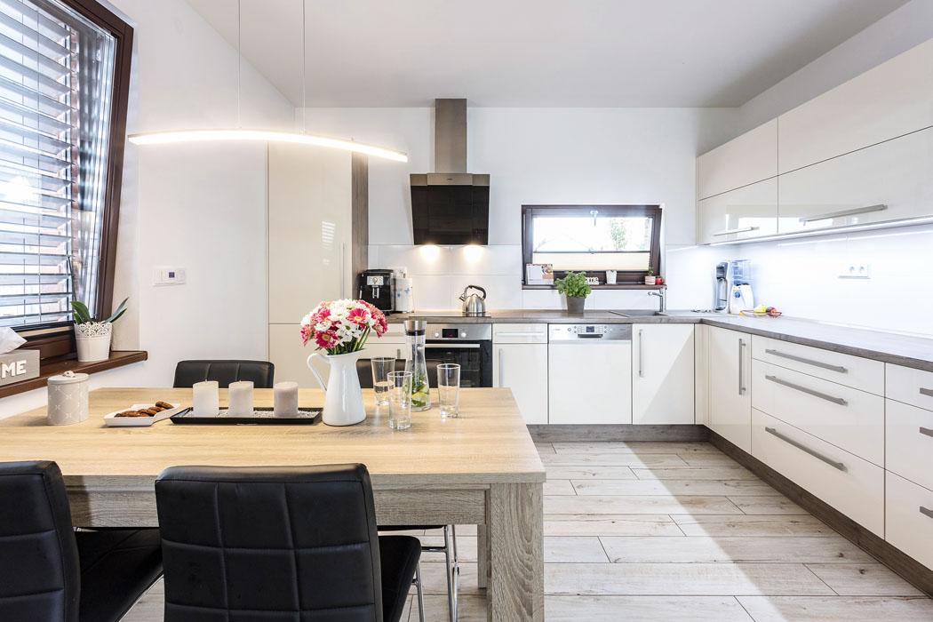 """Velkoryse pojatá kuchyňská linka ve tvaru písmene """"L"""" v decentní světlé krémové barvě zaujímá spolu s jídelním stolem asi třetinu plochy hlavní obytné místnosti v domě."""