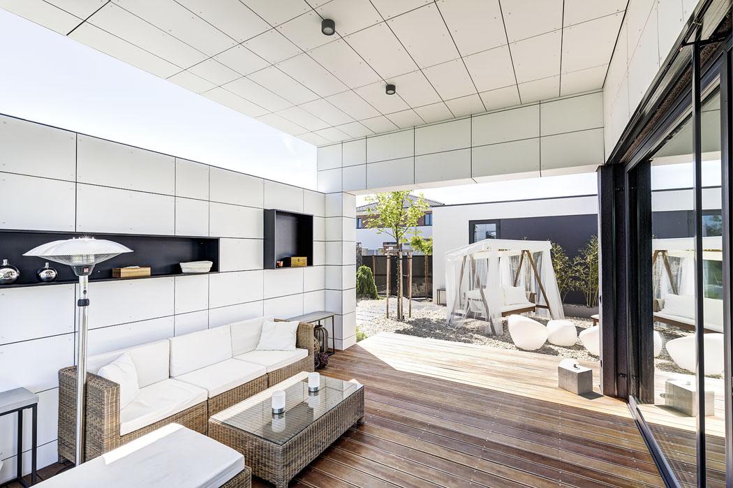 Krytá terasa je zařízena jako venkovní obývací pokoj, včetně osvětlení anik sdrobnými dekoracemi.
