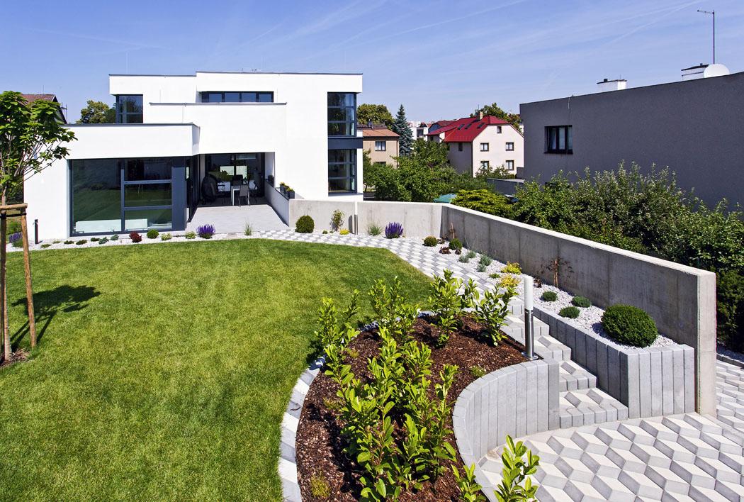 Kvalitní trávník vkombinaci sněkolika okrasnými aužitkovými záhony achodníčky ze zámkové dlažby představují ideální, takřka bezúdržbovou zahradu pro ty, kdo se chtějí plně věnovat práci ařadě zálib.