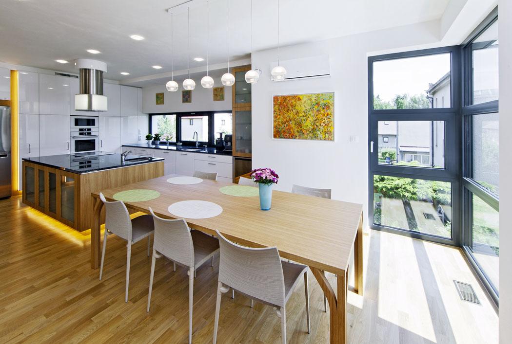 Jídelní stůl přímo navazuje navarné centrum. Atraktivitu střízlivého interiéru zvyšuje rozptýlené osvětlení, LED svítidla jsou zakomponována dostropu anábytku.