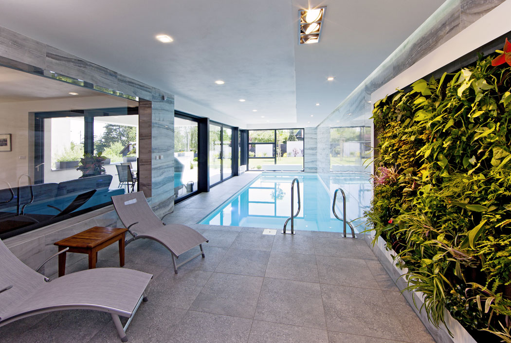Bazén sprosklenými stěnami působí jako pokračování zahrady vinteriéru. Kvetoucí zelená stěna sem přináší svěžest aživé barvy přírody.