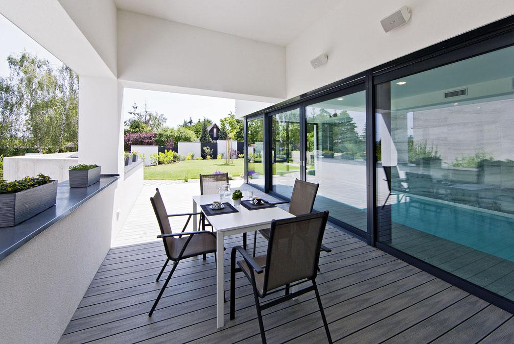 Terasa má praktickou atrvanlivou podlahu zdřevoplastu. Majitelé domu velmi oceňují efekt zvýšeného stropu – teplo stoupá vzhůru aposezení ustolu je ivlétě příjemné.