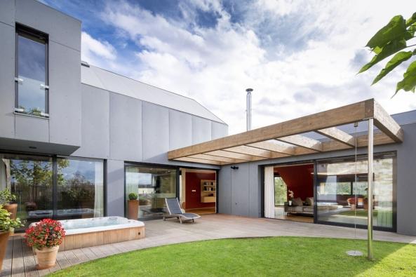 Dům má šikmé betonové střechy, což není běžné, ale dobře izolují avlétě pod nimi bývá příjemně ibez použití klimatizace. Majitelé si pochvalují i propojení interiéru s exteriérem.