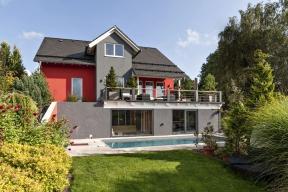 Projektanti ze společnosti Haas Fertigbau se museli vypořádat svelmi svažitým terénem parcely, na druhé straněnáročné terénní úpravy přidaly domu na zajímavosti.