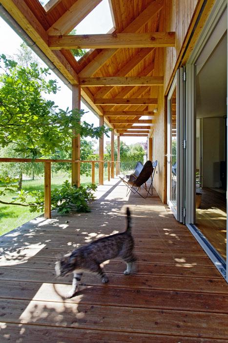 """Krytá terasa podél celé jižní strany domu vtvoří zahezkého počasí jakýsi """"venkovní obývák"""". Okno vpřesahující střeše je pojistkou proti nedostatku denního světla jak naterase, tak vinteriéru."""