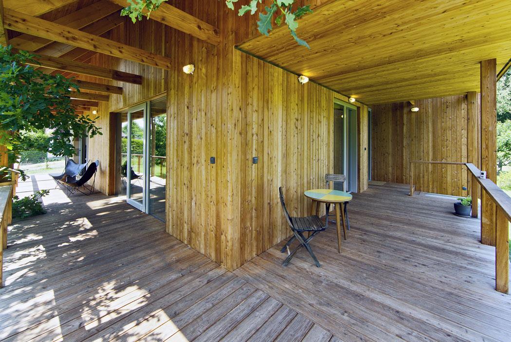 """Navýchodní straně terasa """"zahýbá zaroh"""" arozšiřuje se tak, aby zde bylo možné umístit stolování. Veškeré dřevo včetně viditelných částí krokví je zmodřínu apěkně přirozeně zestárne."""
