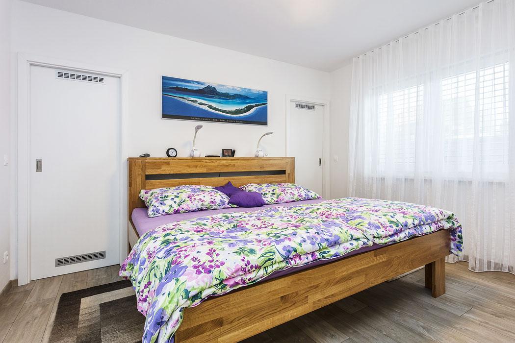 Interiér ložnice je nesen ve znamení přírodního dřeva. Dveře za postelí vedou do šaten, protože Karel a Sylva si v novém domě přáli mít každý svoji šatnu, aby se vyhnuli zbytečným skříním.