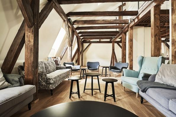 Zrekonstruované podkroví je vybaveno nábytkem vretro stylu aslouží krelaxaci. Historický krov architekti zkombinovali smoderními konstrukčními prvky ze skla aoceli.