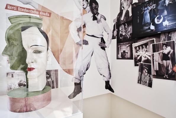 Expozice věnovaná Osvobozenému divadlu na řadě dobových fotografií připomíná jednotlivá představení iherce. Černobílé klaunské líčení sčervenými prvky patří kjeho symbolům.