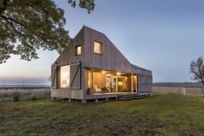 Posuvné okenice umožňují dům zcela otevřít i naopak uzavřít do kompaktního tvaru. Mezery mezi dřevěnými profily propouštějí světlo, takže interiér nezůstává ve tmě.