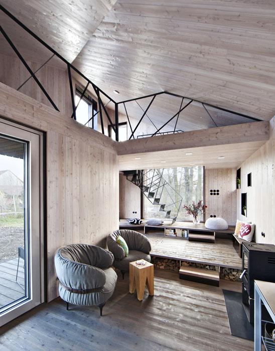 """Prostor u jižního okna tvoří dvoustupňové pódium určené k odpočinku a odkládání věcí. Kromě otevřených přihrádek jsou tu další úložné prostory, ukryté pod odklápěcí částí """"podlahy""""."""
