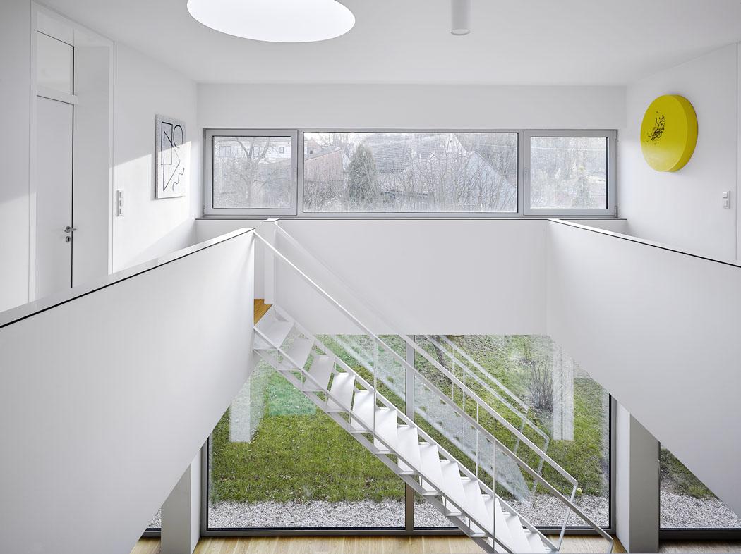 Největším luxusem domu je jeho přímá vazba na zahradu, která se promítá téměř do každé místnosti. Neruší ji ani ocelové schodiště, přestože přechází téměř přes celou čelní stěnu obývací haly.