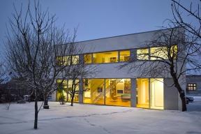 Zimní atmosféra ještě zvýrazňuje střízlivou estetiku domu, založenou na principech  funkcionalistické architektury: elementární geometrické tvary, pásové prosklené plochy,  hladké bílé fasády, žádné zbytečné prvky...
