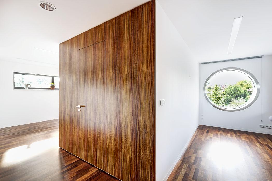 """Vpracovně nabízí okno vedle vestavěné šatny magický pohled dozeleně vkruhovém rámu, aproto se stala nejoblíbenějším místem pána domu. Okna jsou zasklena trojskly alemována speciální kovovou """"manžetou"""" dle návrhu architektů. Tyto originální prvky, podobně jako sokly lícující somítkou či obklady adveře snavazující kresbou dýhy jsou vizitkou precizně provedené práce."""