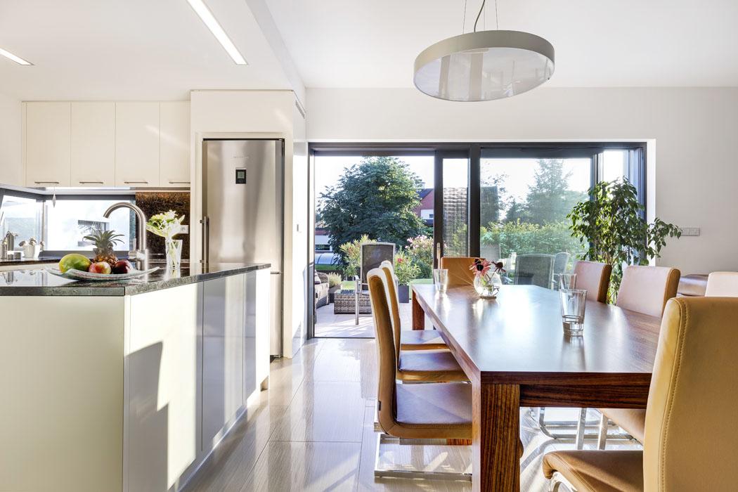 Společné obývací části dominuje prosklená stěna naterasu ataké masivní jídelní stůl sdekorativní ušlechtilou dýhou ovangol, která byla použita inanábytek.