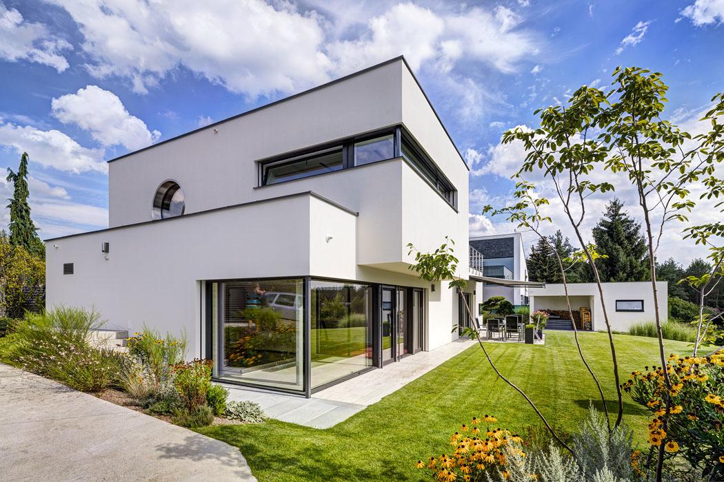 Pohled odgaráže zvýrazňuje kompozici zpřesahujících se kvádrů arohové pásové prosklené plochy – jeden zcharakteristických znaků funkcionalistické architektury.