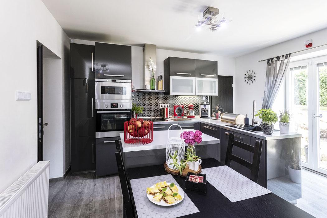 Kuchyňská sekce skuchyňskou linkou ajídelní část hlavní obytné místnosti vpřízemí je prosvětlena prosklenými dveřmi, kterými se dostanete naterasu anazahradu.