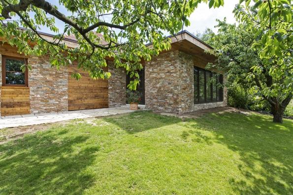Přístavba rodinného domu je obložena pískovcem adřevem tak, aby harmonicky zapadla dozahrady.