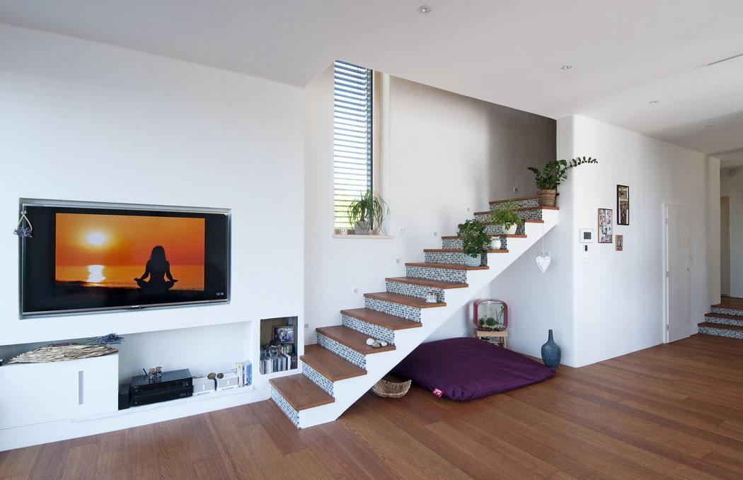 Schodišťové stupně jsou vyrobeny ze stejného materiálu jako podlaha, zpřírodního dubu. Schodiště oživuje modrobílá mozaika.