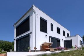 Jednoduchý tvar domu umožňuje eliminovat vznik tepelných mostů, což je uenergeticky úsporných staveb velmi důležité.  Díky velikým prosklením získává dům vzimě pasivní solární zisky. Naopak, kvalitní žaluzie napojené nainteligentní systém ovládání brání vlétě přehřátí interiéru.