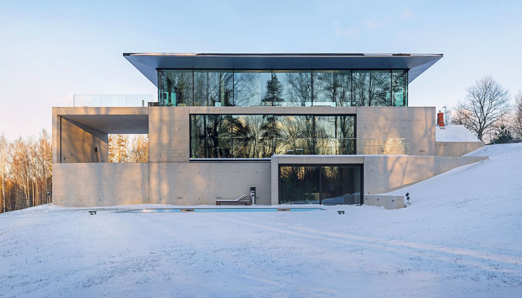 Architekti studia OUTOFBOX tomu říkají asketický design. Impozantní budova ze skla a betonu organicky zapadá do terasovitého terénu.