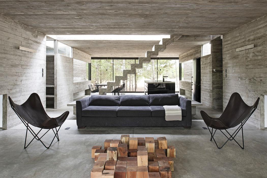 Dům sám osobě architekti pojali vpodstatě jako monolitní sochařské dílo. Proto vinteriéru stačí jen pár zajímavých solitérů, například křesílka astolek, který lze složit zkostek ztropického dřeva.