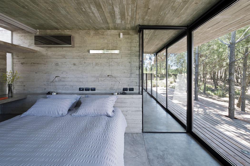 Bariéru mezi domem alesem tvoří jen sklo atenké hliníkové okenní profily. Přesahující betonový strop chrání terasu před deštěm aložnice před přehříváním.