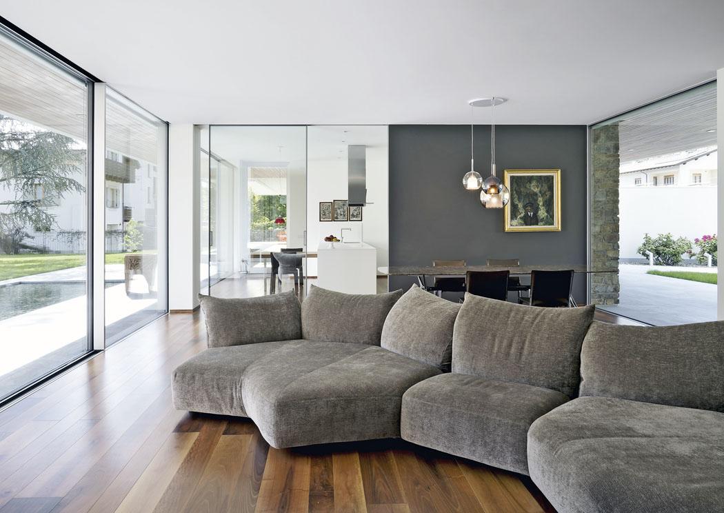 """Obývací pokoj ijídelna jsou příčně transparentní, prosklené plochy se subtilními obvodovými rámy abezbariérovými podlahovými přechody budí dojem, že zahrada ze severu najih volně prochází domem.Nábytku je minimum, luxusní """"kusy"""" prestižních značek Edra aCassina korunují dům svou elegancí."""