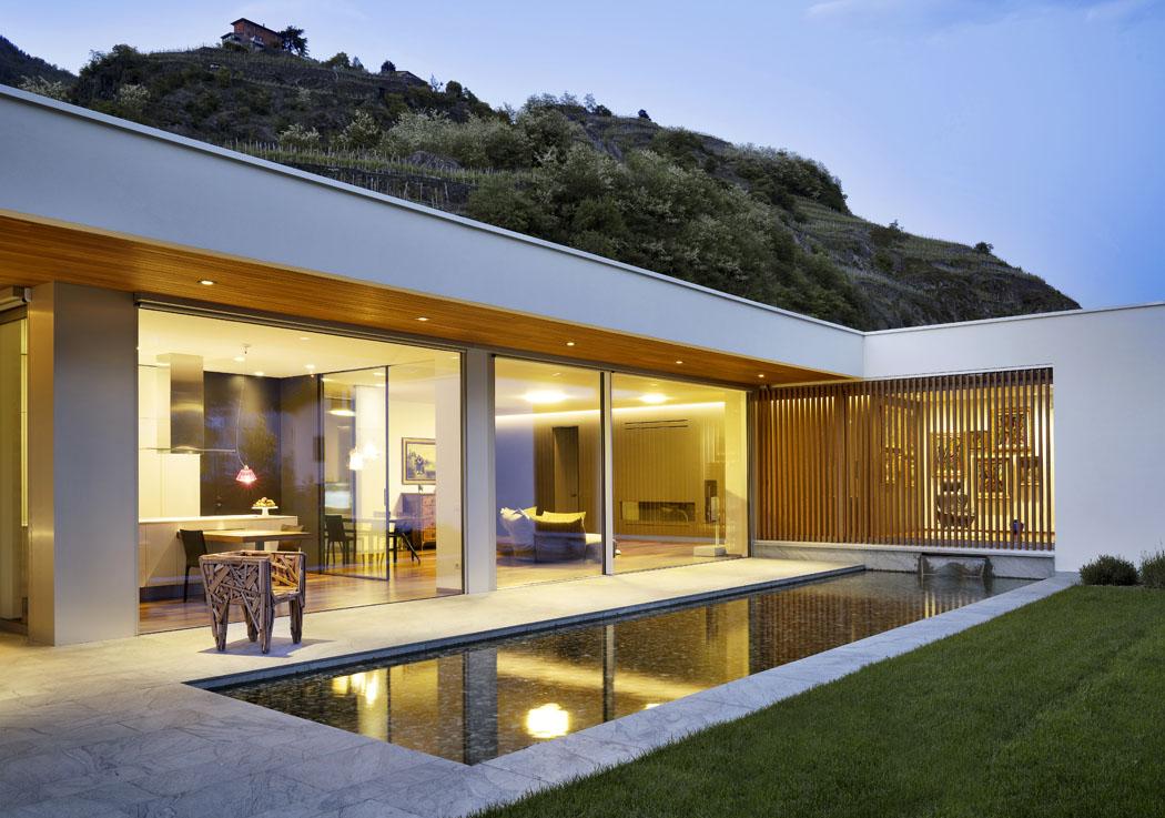 Při večerním osvětlení je nejlépe patrné maximální otevření společenské části domu dozahrady. Umožňují to skleněné tabule ošířce více než čtyři metry.