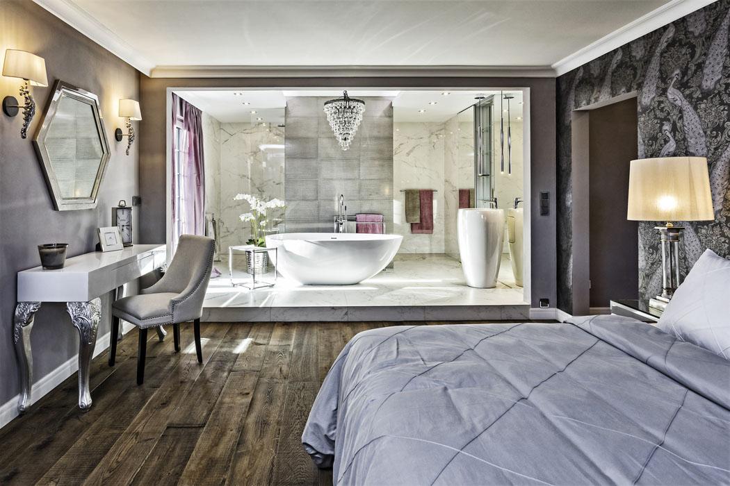 Zlatým hřebem interiéru je ložnice. Dřevěná podlaha skrásnou rustikální strukturou rafinovaně přechází vmramorový sokl, naněmž je jako nadivadelní scéně umístěna otevřená koupelna vhlavní roli snádherně tvarovanou solitérní vanou