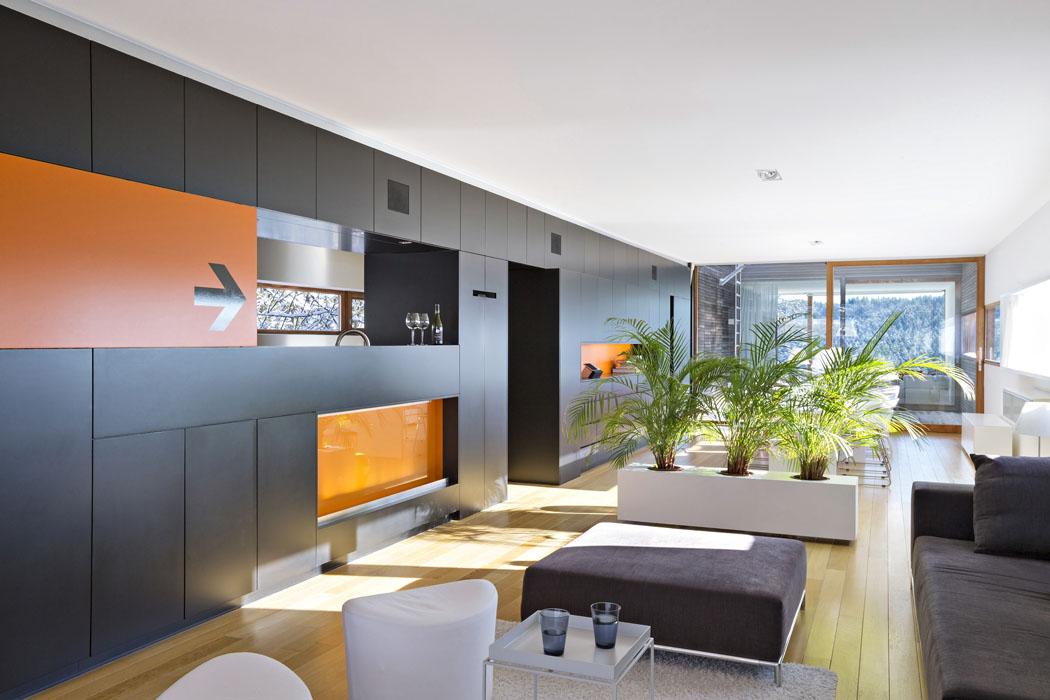 """Patro je podélnou nábytkovou stěnou rozděleno nahlavní obývací část aúzký prostor – pasáž podél severní fasády, která má obslužnou akomunikační funkci. Prosklenou stěnou je vidět přes terasu až do""""televizního"""" pokoje snejkrásnějším výhledem."""