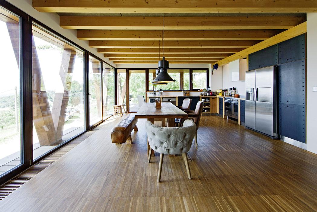 Hlavní obytná místnost je ze dvou stran prosklená. Základ tvoří podlaha zdřevěné průmyslové mozaiky, zařízení je volnou směsicí stylů odpřírodního poindustriální. Nejdůležitější bylo vytvořit harmonické prostředí, kde budou přítomné vzpomínky akde se rodina bude cítit dobře.