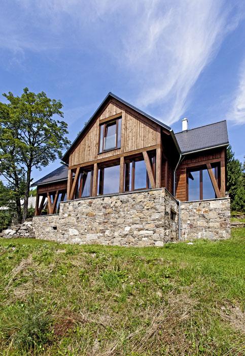 Podezdívka zmístního kamene jako by zoka vypadla původním starým zídkám napozemku ivokolí. Prosklená fasáda ustupující zašikmýni trámovými podpěrami je příjemně stíněná přesahující konstrukcí. Toto řešení je citlivým kompromisem mezi moderní atradiční architekturou.