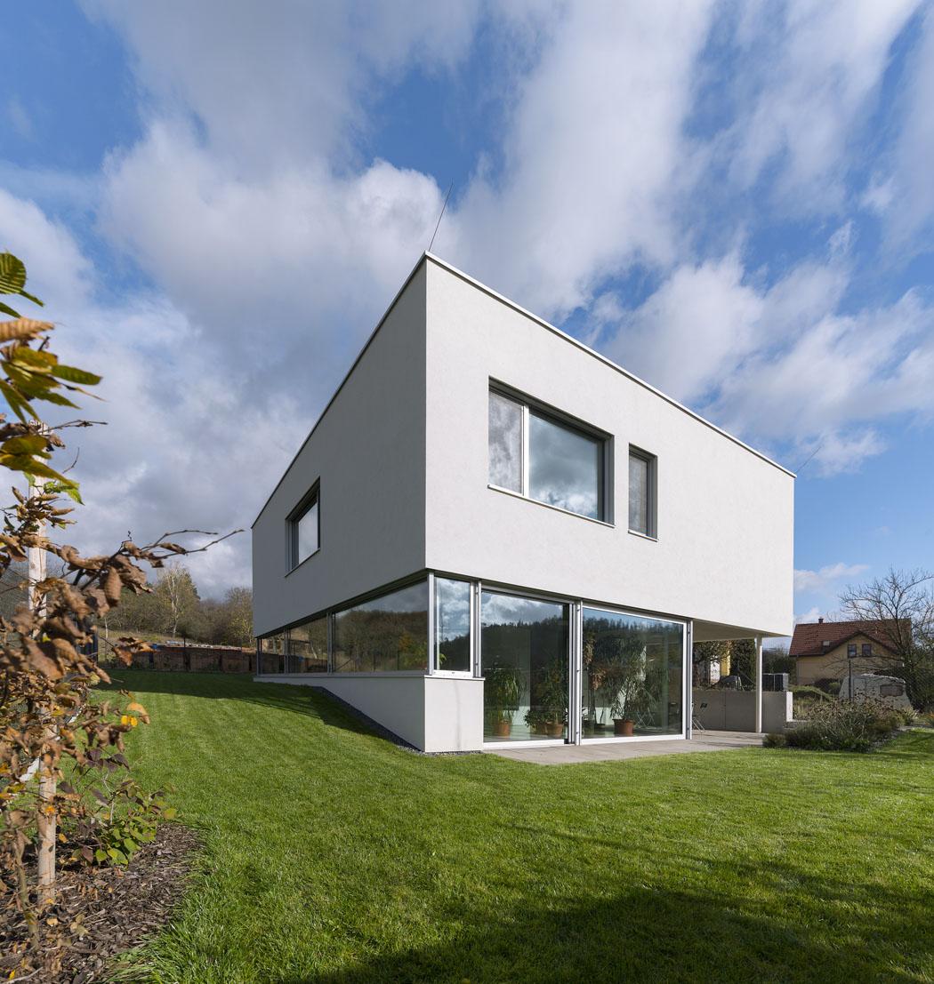 Stavba kubických tvarů s plochou střechou je částečně zapuštěna do mírně svažitého terénu se severojižní orientací. Klíčové pro celý projekt je co největší vizuální propojení s exteriérem.