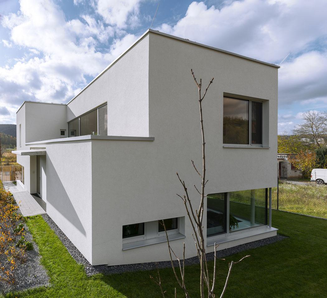 Dům na masivně zastavěné parcele působí odlehčeným dojmem. Přispívá k tomu i bílá omítka na fasádě se samočisticím účinkem, hliníkové přírodně eloxované okenní rámy či bohatost zasklení v různých formátech.