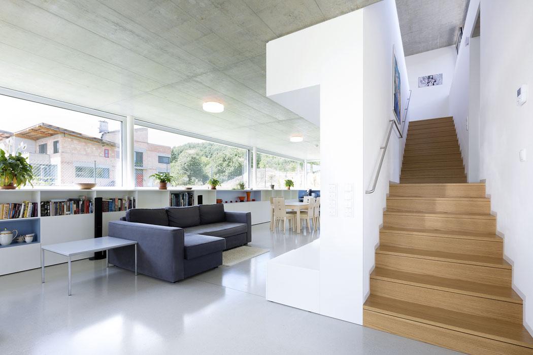Čisté ajednoduché linie interiéru spoluutvářejí pohledové železobetonové stropy alité cementové podlahy Cemflow Look vjednotném přírodním provedení. Zbroušené kamínky dávají podlaze zajímavý vzhled aoriginalitu. Celá podlaha je natřena ochranným matným lakem. Pouze vkolárně atechnickém koutě se nachází keramická dlažba orozměru 60 x 60cm.
