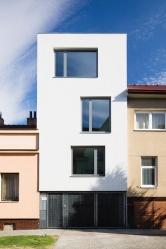 Při rekonstrukci řadového domu architekt JanKyzlink navrhl směrem dozahrady moderní prosklenou přístavbu propojenou sterasou avodní plochou. Bydlení tak získalo úplně novou dimenzi. Směrem doulice hledí střízlivá moderní architektura.