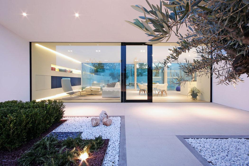 Navýchodní straně domu je malá zahrada, zníž je vidět přes hlavní obývací část, terasu abazén až naopačný konec pozemku. Velkoplošné bezrámové zasklení vytváří zcela transparentní efekt, jen dveře architekt zvýraznil černým rámem.