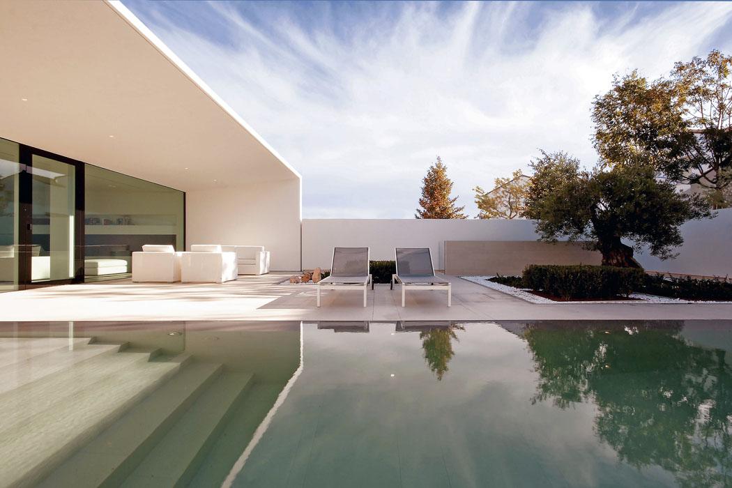 Před hlavním obytným prostorem je terasa stíněná tři metry hlubokým přesahem střechy. Další stín dává starý olivovník, který se při stavbě podařilo zachovat.