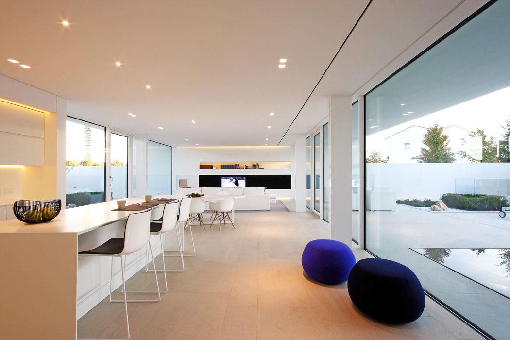 Interiéru vládne bílá vkombinaci se světlými přírodními barvami, zvnitřní strany jsou bílé iokenní rámy. Dům byl vybaven nábytkem navrženým namíru zdesek zvysokotlakého laminátu sintegrovaným LED osvětlením aelektronikou, dojídelny architekt vybral skořepinové židle odCharlese Eamese. Matná kamenná dlažba bezbariérově přechází naterasu akbazénu.
