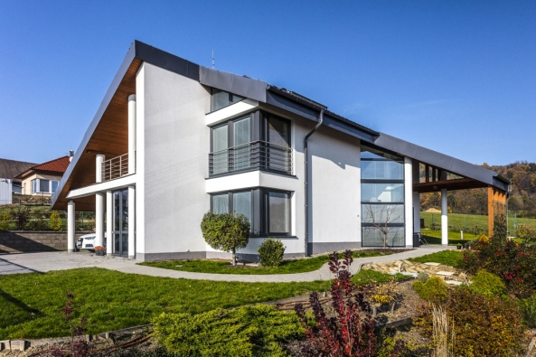 Zvolený tvar domu citlivě pracuje stvarem svažitého pozemku ijeho orientací. Hmotová konfigurace domu je tradiční, ale nepostrádá některé progresivní architektonické prvky.