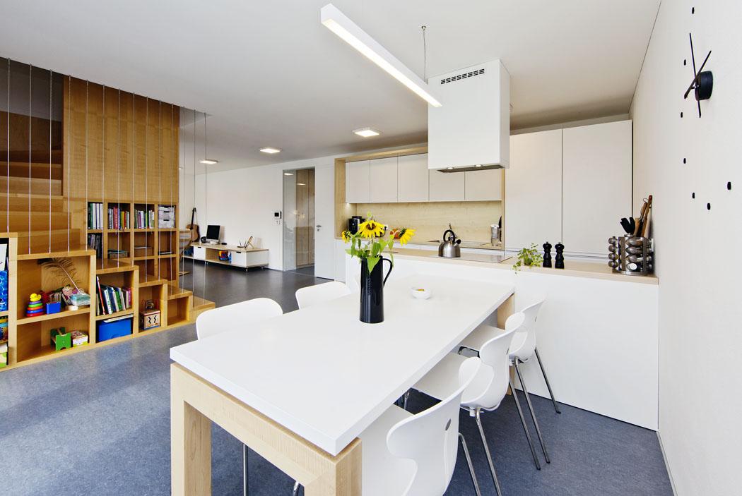 Kuchyňská linka ajídelní stůl byly vyrobeny zlakovaných alaminovaných MDF desek. Úspornost ačistotu interiéru dotvářejí hladké povrchy, kompaktní tvary aintegrované prvky.