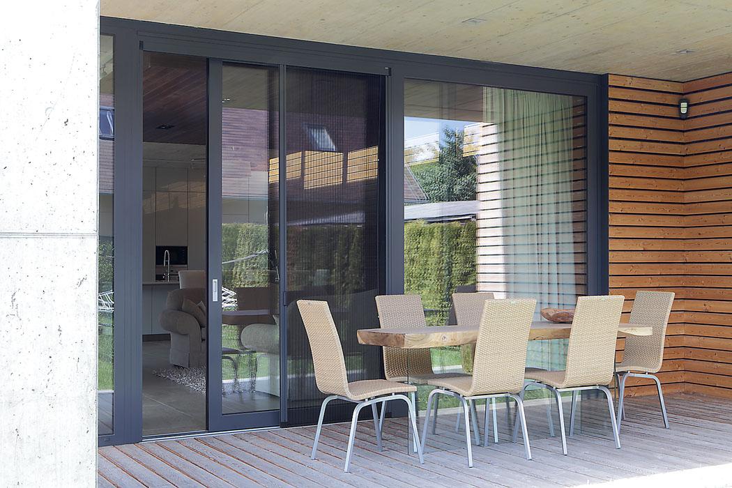 Posunutím skleněné stěny se obývací pokoj rozšíří ven. Velký přesah stropní desky umožňuje stolovat naterase povelkou část roku atéměř zakaždého počasí.